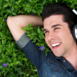 Royalty-Free Stock Photo: Young man lying on grass smiling with headphones