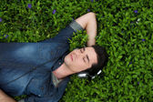 Young man resting in the grass with eyes closed listening to music on headphones — Stock Photo