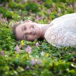 Beautiful young woman lying on grass with flowers — Stock Photo