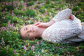 Attractive young woman lying on grass and flowers — Stock Photo