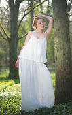 Elegant woman in long white dress standing in the forest — Stock Photo