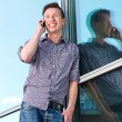 Happy young man on mobile phone outdoors  — Stock Photo
