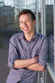Handsome young man smiling outoors — Stock Photo