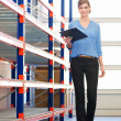 Businesswoman standing in next to shelves in warehouse with clipboard — Stock Photo