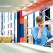 Businesswoman on the phone and checking inventory in warehouse — Стоковая фотография