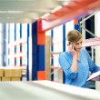 Businesswoman on the phone and checking inventory in warehouse - Stock Photo