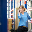 Stock Photo: Casual female warehouse employee talking on mobile phone