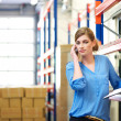 Female logistics worker on mobile phone in warehouse — Stock Photo