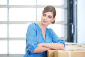 Portrait of a businesswoman relaxing next to boxes in warehouse — Stock Photo