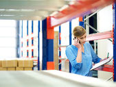 Businesswoman on the phone and checking inventory in warehouse — Stock Photo