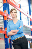 Confident business woman relaxing next to shelve racks in warehouse — Photo