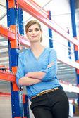 Säker affärskvinna avkopplande nästa att skrinlägga rack i lager — Stockfoto