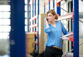 Casual female warehouse employee talking on mobile phone — Stock Photo