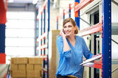 Female logistics worker controlling stock and talking on cellphone in warehouse — Stock Photo