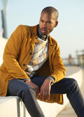 Handsome male fashion model sitting outdoors — Stock Photo