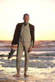 Happy african american man standing on the beach — Stock Photo