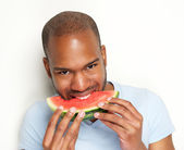 Young man smiling and eating delicious watermelon — Stock Photo