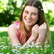 Portrait of a happy young woman lying outdoors on grass and flowers — Stock Photo