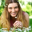 Beautiful young woman holding flower in the park — Stock Photo