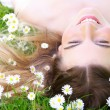 Young woman lying on grass with flowers in the park — Stock Photo #26614319