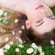 Young woman lying on grass and flowers outdoors — Stock Photo #26614331