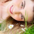 Portrait of a beautiful woman lying in the park with flowers — Stock Photo
