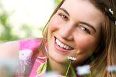 привлекательный молодой женщины, улыбаясь с цветком на открытом воздухе — Стоковое фото
