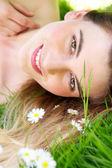 Portret pięknej kobiety leżący w parku z kwiatami — Zdjęcie stockowe