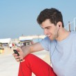 Portrait of a handsome young man listening on mp3 player outdoors — Stock Photo