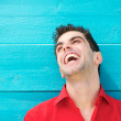 Portrait of a young man in red shirt laughing — Stock Photo