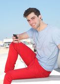 Handsome young man listening to music on mp3 player — Stock fotografie