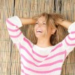 Beautiful blond woman standing outdoors laughing with hands in hair — Stock Photo