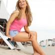 Beautiful blond woman laughing at the beach — Stock Photo