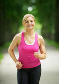 Porträtt av en aktiv ung kvinna jogga i parken — Stockfoto
