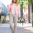 Stock Photo: Beautiful young woman walking in the city with bag