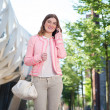 Young woman walking and talking on mobile phone — Stock Photo #27358361