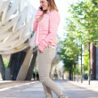 Young woman talking on mobile phone in the city — Stock Photo