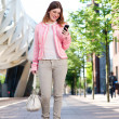 Young woman walking outdoors and text messaging on mobile phone — Stock Photo