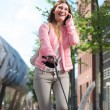 Woman walking dog and calling by phone outdoors — Stock Photo