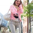 Happy young woman walking her dog in the city and talking on the phone — Stock Photo #27358495