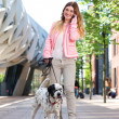 Female walking her dog outdoors and talking on mobile phone — Stock Photo