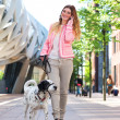 Woman walking dog and talking to friends on mobile phone — Stock Photo