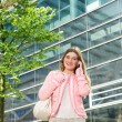 Young woman talking on mobile phone outside city building — Stock Photo