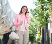 Young woman walking and talking on mobile phone — Stock Photo