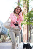 Happy young woman walking her dog in the city and talking on the phone — Stock Photo