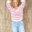 Beautiful blond woman laughing with hands in hair — Stock Photo