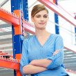 Confident business woman standing in warehouse — Stock Photo