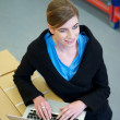 Warehouse employee typing on laptop computer  — Stockfoto