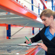 Portrait of a businesswoman writing on clipboard in warehouse — Stock Photo