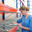 Female warehouse employee standing next to shelves and writing on clipboard — Stock Photo